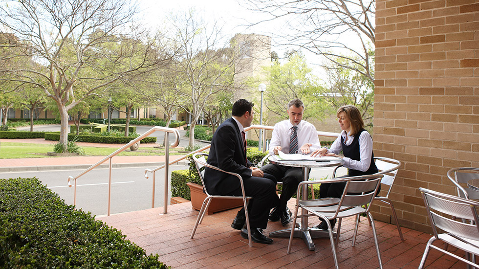 Three colleagues talking in an outdoor dining area on the ground of MGSM north ryde