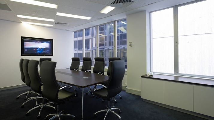 A room resembling a boardroom with high-backed chairs